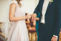 A noiva põe uma aliança de casamento sobre um dedo dos noivos fotografia de stock royalty free