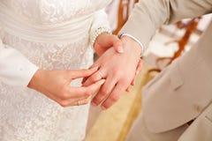 A noiva pôs a aliança de casamento sobre o noivo Fotografia de Stock
