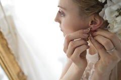 Noiva para pôr os brincos Fotografia de Stock Royalty Free