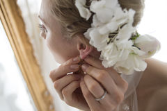 Noiva para pôr os brincos ao olhar no espelho Fotografia de Stock