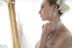 Noiva que está na frente de um espelho Fotografia de Stock