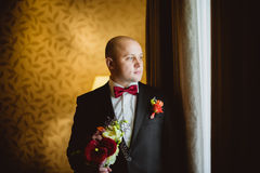 A noiva que está perto de uma janela com ramalhete Fotografia de Stock Royalty Free