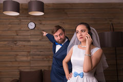 Noiva que fala pelo telefone, noivo que mostra no relógio Fotografia de Stock Royalty Free