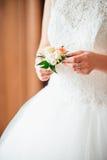 Noiva que guarda o boutonniere do casamento nas mãos Fotografia de Stock Royalty Free