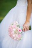 Noiva que guarda o ramalhete do casamento das flores fotografia de stock