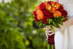 Noiva que guarda o ramalhete vermelho e alaranjado das flores Imagem de Stock
