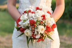 Noiva que guarda seu ramalhete de flores vermelhas e brancas Imagens de Stock