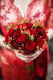 Noiva que guarda seu ramalhete vermelho do casamento das flores Fotografia de Stock Royalty Free