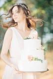 Noiva que guarda um bolo de casamento Fotos de Stock