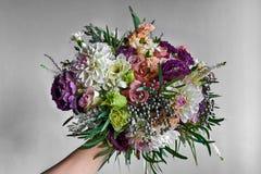 Noiva que guarda um ramalhete do casamento em uma mão com as pétalas vermelhas, cor-de-rosa e brancas coloridas Fotos de Stock Royalty Free
