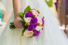 Noiva que mantém o ramalhete violeta do cravo do casamento contra o vestido Foto de Stock Royalty Free