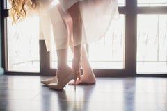Noiva que põe sobre suas sapatas Os detalhes fazem a diferença contra janelas panorâmicos do fundo fotos de stock royalty free