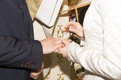 Noiva que põe uma aliança de casamento sobre o dedo do ` s do noivo Fotos de Stock Royalty Free