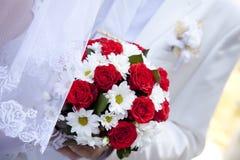 Noiva que prende as rosas vermelhas bonitas que wedding o ramalhete Imagem de Stock Royalty Free