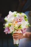 Noiva que prende flores cor-de-rosa bonitas do casamento Fotos de Stock Royalty Free