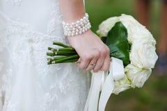 A noiva que prende o casamento branco floresce o ramalhete Fotos de Stock Royalty Free