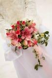 A noiva que prende o ramalhete cor-de-rosa do casamento Imagens de Stock
