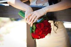 Noiva que prende um ramalhete do casamento Imagens de Stock Royalty Free