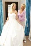 Noiva que tenta no vestido de casamento com as vendas assistentes imagens de stock royalty free