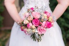 A noiva realiza em seu ramalhete do casamento das mãos com rosas cor-de-rosa Imagens de Stock Royalty Free