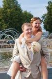 A noiva senta-se em uma parte traseira no noivo Imagem de Stock Royalty Free