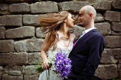 A noiva toca na cara do noivo com seu cabelo que está atrás de uma pedra Fotografia de Stock Royalty Free
