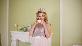 A noiva toma uma xícara de café da cornija de lareira e toma um sorvo video estoque