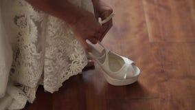 A noiva veste as sapatas brancas do casamento com suas mãos video estoque