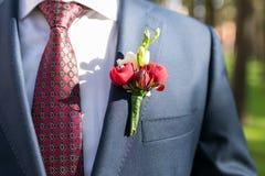 Noivo à moda no casaco azul, na camisa branca e no laço vermelho com boutonniere fotos de stock