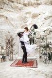 Noivo africano e noiva caucasiano que abra?am-se em um estilo do boho antes do arco do casamento das flores frescas groom imagens de stock
