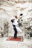 Noivo africano e noiva caucasiano que abra?am-se em um estilo do boho antes do arco do casamento das flores frescas groom fotos de stock royalty free