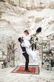 Noivo africano e noiva caucasiano que abra?am-se em um estilo do boho antes do arco do casamento das flores frescas groom imagens de stock royalty free