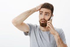 Noivo ansioso interessado e incomodado que recebe más notícias durante o telefonema que guarda o braço na testa que olha à esquer foto de stock