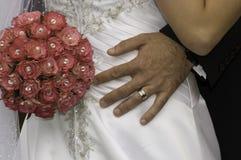 Noivo com sua mão e ramalhete vermelho em sua noiva Fotos de Stock