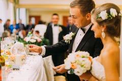 Noivo considerável que guarda a redenção da noiva no casamento dentro foto de stock
