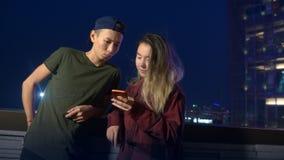 Noivo e amiga asiáticos novos felizes dos pares use um smartphone ao estar em uma rua da cidade na noite filme