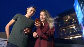 Noivo e amiga asiáticos novos felizes dos pares use um smartphone ao estar em uma rua da cidade na noite vídeos de arquivo