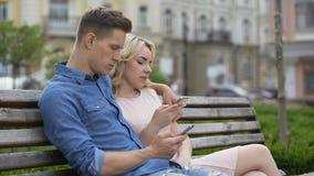 Noivo e amiga que sentam-se no banco, redigido nos telefones, trabalhos em rede video estoque
