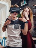 Noivo e amiga que testam os auriculares novos da visão do vr 3d que passam o tempo junto que tem o divertimento que ri em casa Imagens de Stock Royalty Free