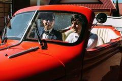 Noivo e amigo no carro vermelho velho Fotos de Stock Royalty Free