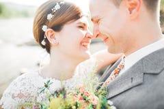 Noivo e noiva à moda delicados elegantes perto do rio com pedras Pares do casamento no amor Imagem de Stock