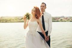 Noivo e noiva à moda delicados elegantes perto do rio ou do lago Pares do casamento no amor Fotografia de Stock Royalty Free
