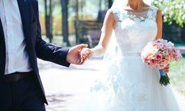 Noivo e noiva elegantes com o ramalhete do casamento que guarda as mãos Pares do casamento fotografia de stock royalty free