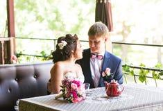 Noivo e noiva felizes junto no café que tem o divertimento Pares felizes do recém-casado no casamento Imagem de Stock Royalty Free