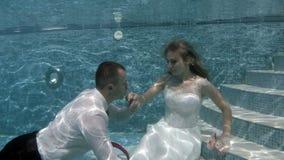 Noivo e noiva felizes no vestido de casamento branco que senta-se debaixo d'água na parte inferior da associação filme