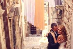 Noivo e noiva fora em uma rua estreita em seu dia do casamento Fotografia de Stock