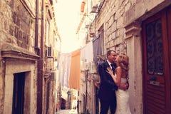 Noivo e noiva fora em uma rua estreita em seu dia do casamento Imagem de Stock Royalty Free