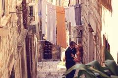 Noivo e noiva fora em uma rua estreita em seu dia do casamento Fotografia de Stock Royalty Free