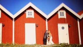 Noivo e noiva perto das casas vermelhas Imagem de Stock Royalty Free