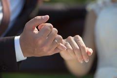 Noivo e noiva que fazem uma promessa do dedo mínimo fotografia de stock